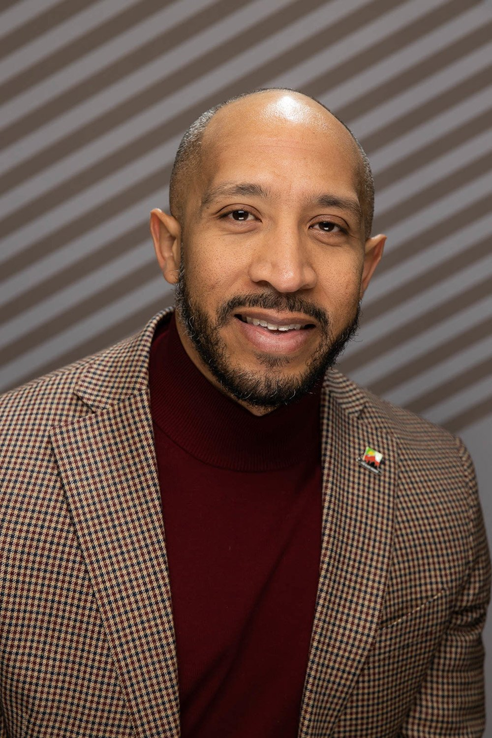 Portrait of James Jackson he sits in a brown checked suit with a maroon sweater in front of a brown and gray diagonal striped wall