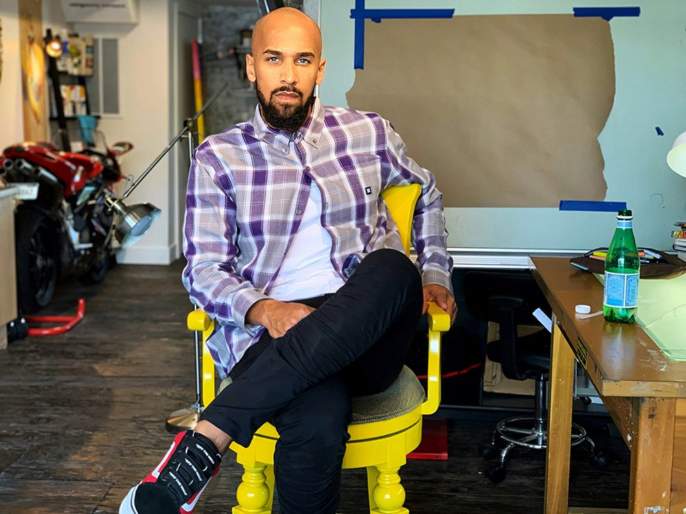 Matthew Sketch sits in a yellow chair his studio, a whiteboard with paper tapped to it is in the backgound, he has a shaved head, wears a purple plaid shirt and black jeans