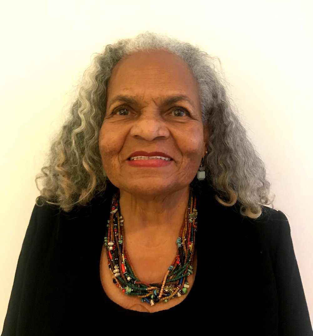 A tightly cropped portrait of Ruth Gooden standing againt a white wall, she wears a black suit jacket with a chunky beaded necklace, she has shoulder-length natural gray hair.